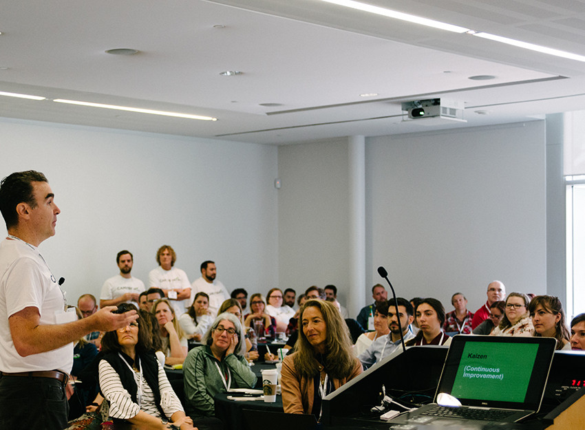 a room full of people listening to someone give a talk