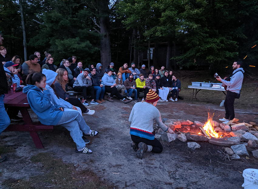 people outside by a campfire