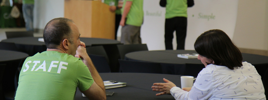 """A man and woman sitting at a table talking. The man has a green shirt labelled """"Staff""""."""