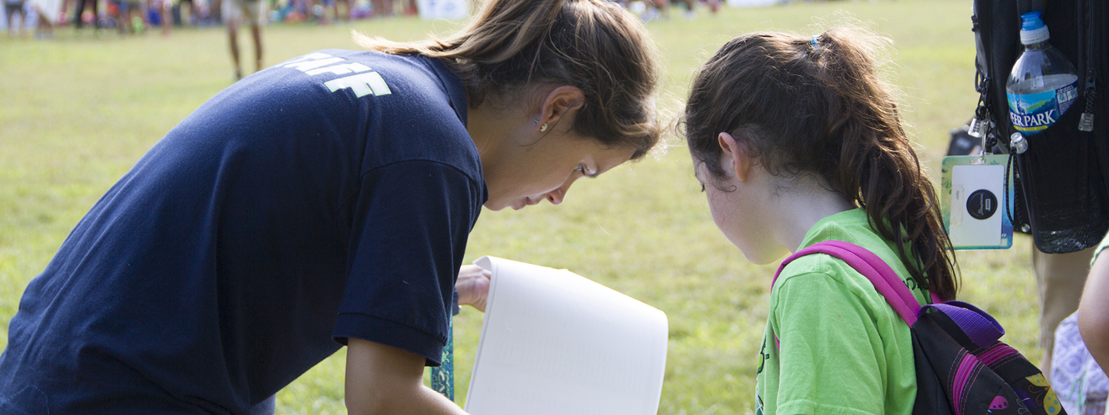 a counsellor showing a camper something