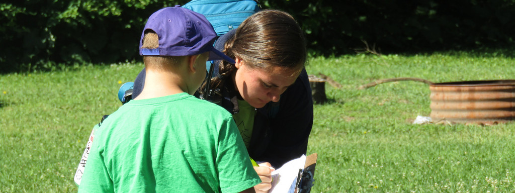 Boy in a purple hat watching a woman kneeling and writing on a clipboard